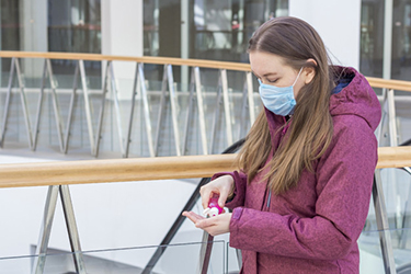 Viral disease prevention concept. Young woman in a medical prote